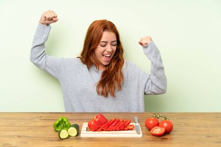 Teenager redhead girl with vegetables in a table celebrating a victory