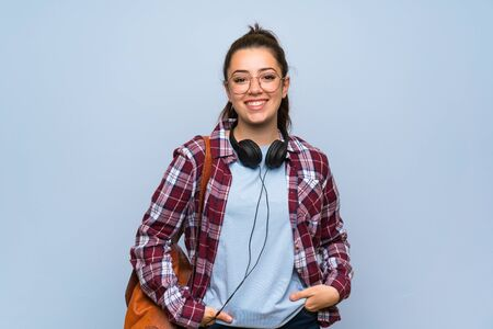 Teenager student girl over isolated blue wall laughing