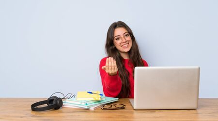 Teenager student girl studying in a table inviting to come with hand. Happy that you came