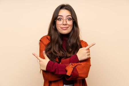 Teenager girl with coat pointing to the laterals having doubts
