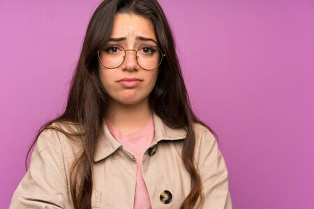 Teenager girl over purple wall sad