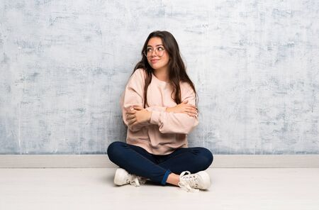 Teenager student girl studying in a table making doubts gesture while lifting the shoulders