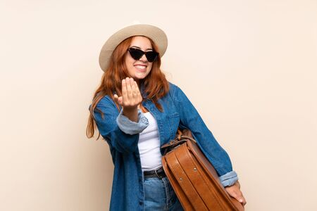 Redhead traveler girl with suitcase over isolated background inviting to come with hand. Happy that you came