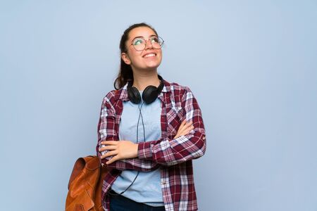 Teenager student girl over isolated blue wall looking up while smiling