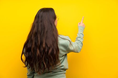 Teenager girl with sweatshirt pointing back with the index finger