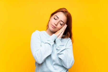 Teenager redhead girl over isolated yellow background making sleep gesture in dorable expression