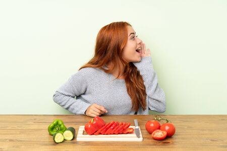 Teenager redhead girl with vegetables in a table shouting with mouth wide open