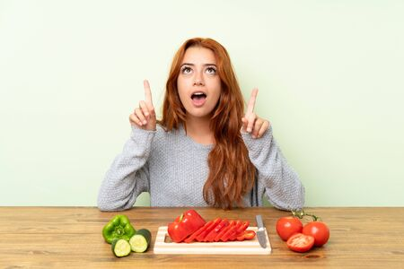Teenager redhead girl with vegetables in a table pointing with the index finger a great idea