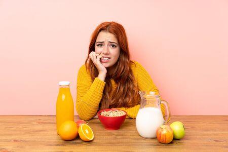 Teenager redhead girl having breakfast in a table nervous and scared Zdjęcie Seryjne