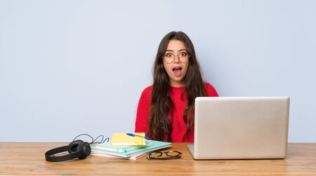Teenager student girl studying in a table with surprise facial expression