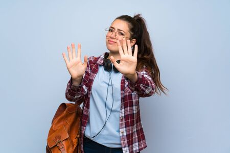 Teenager student girl over isolated blue wall nervous stretching hands to the front Zdjęcie Seryjne