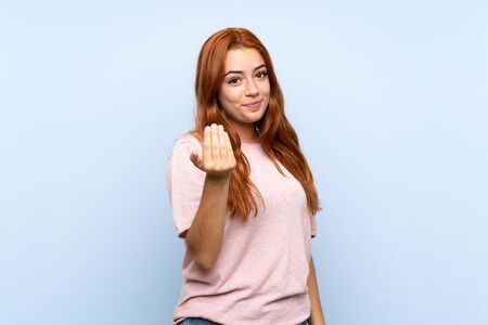 Teenager redhead girl over isolated blue background inviting to come with hand. Happy that you came Standard-Bild