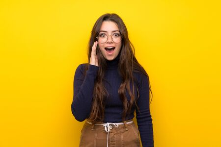 Teenager girl over isolated yellow wall with surprise and shocked facial expression