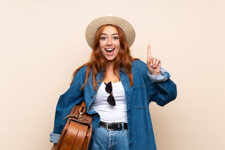Redhead traveler girl with suitcase over isolated background pointing up a great idea