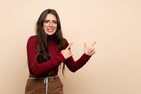 Teenager girl with glasses frightened and pointing to the side