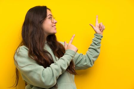 Teenager girl with sweatshirt pointing with the index finger a great idea