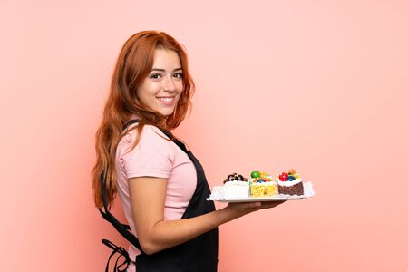 Teenager redhead girl holding lots of different mini cakes over isolated pink background smiling a lot