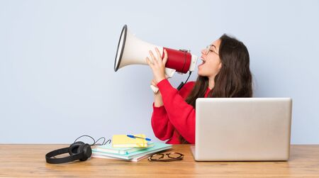 Teenager student girl studying in a table shouting through a megaphone