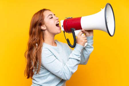 Teenager redhead girl over isolated yellow background shouting through a megaphone Stok Fotoğraf