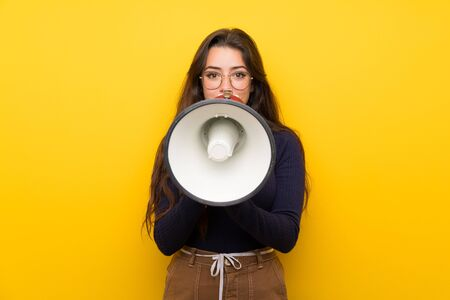 Teenager girl over isolated yellow wall shouting through a megaphone Imagens - 131998156