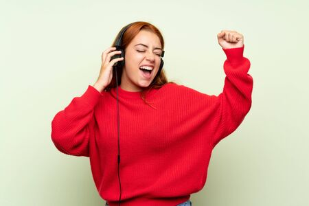 Teenager redhead girl with sweater over isolated green background listening to music with headphones