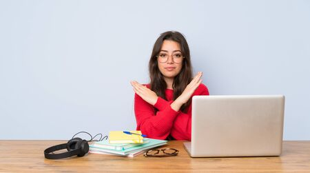 Teenager student girl studying in a table making NO gesture Фото со стока