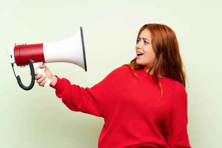 Teenager redhead girl with sweater over isolated green background holding a megaphone