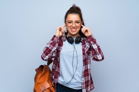 Teenager student girl over isolated blue wall frustrated and covering ears