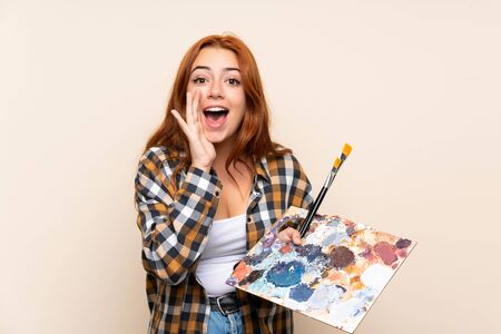 Teenager redhead girl holding a palette over isolated background shouting with mouth wide open Stok Fotoğraf