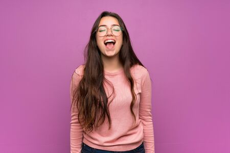 Teenager girl over purple wall shouting to the front with mouth wide open Stok Fotoğraf