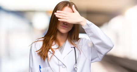 Redhead doctor woman covering eyes by hands. Do not want to see something in the hospital