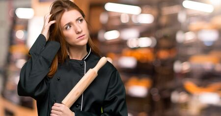 Young redhead chef woman having doubts while scratching head in the bakery