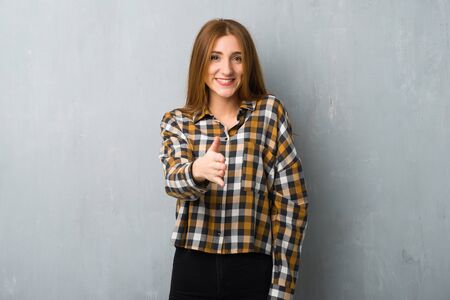 Young redhead girl over grunge wall shaking hands for closing a good deal