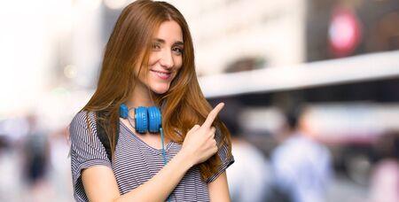 Rothaarige Studentin, die auf die Seite zeigt, um ein Produkt in der Stadt zu präsentieren Standard-Bild