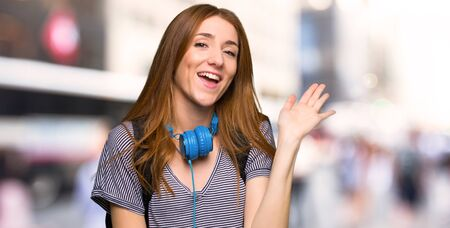 Redhead student woman saluting with hand with happy expression in the city