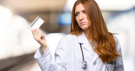 Redhead doctor woman taking a credit card without money in the hospital