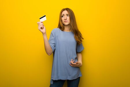 Young redhead girl over yellow wall background taking a credit card without money Archivio Fotografico