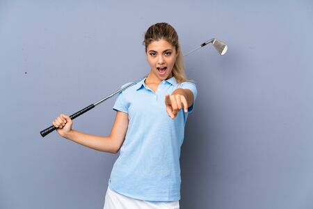 Teenager golfer girl over grey wall surprised and pointing front