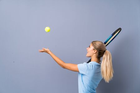 Teenager tennis player girl over grey wall