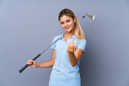 Teenager golfer girl over grey wall inviting to come with hand. Happy that you came