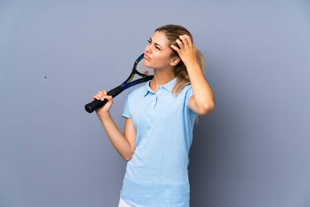 Teenager tennis player girl over grey wall having doubts and with confuse face expression
