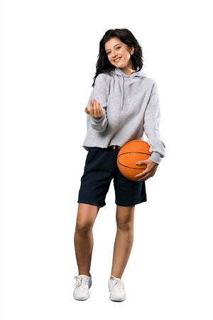 A full-length shot of a Young woman playing basketball inviting to come with hand. Happy that you came over isolated white background