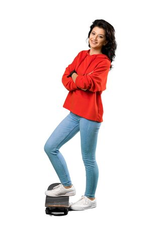 A full-length shot of a Young skater woman with red sweatshirt over isolated white background 版權商用圖片 - 131778699
