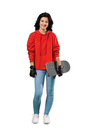 A full-length shot of a Young skater woman smiling a lot over isolated white background 版權商用圖片