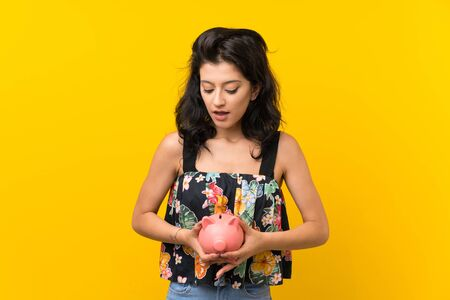 Young woman over isolated yellow background holding a big piggybank