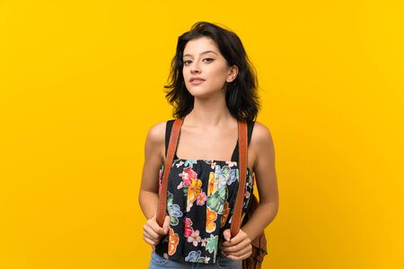 Young woman over isolated yellow background with backpack