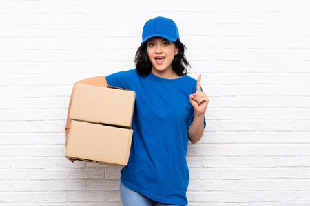 Young delivery woman over white brick wall pointing up a great idea Imagens