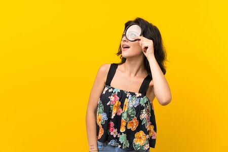 Young woman over isolated yellow background holding a magnifying glass