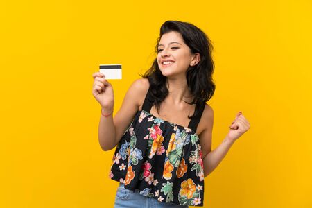 Young woman over isolated yellow background holding a credit card