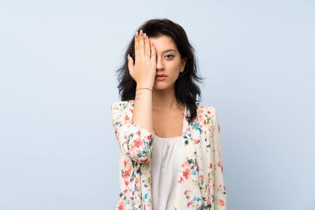 Young woman over isolated blue background covering a eye by hand